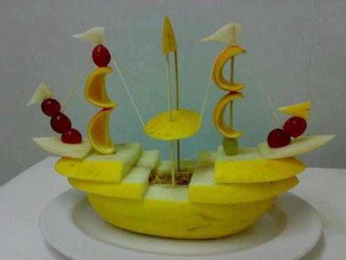 Barco hecho de melón y mástiles de naranja y guindas
