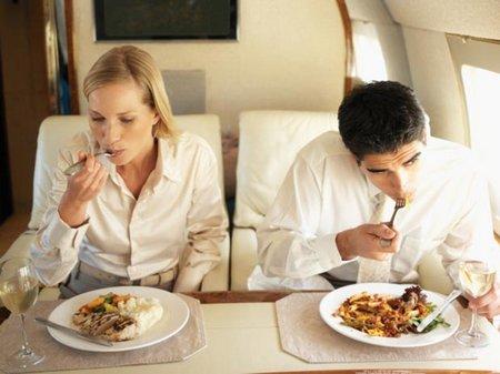Una pareja comiendo en un avión