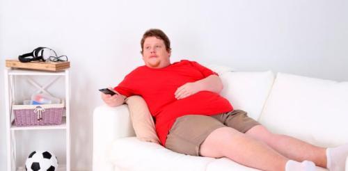 chico obeso tumbado en sofá