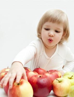 niña rubia cogiendo una manzana