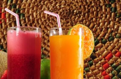 zumos de fresa y naranja sobre fondo tropical